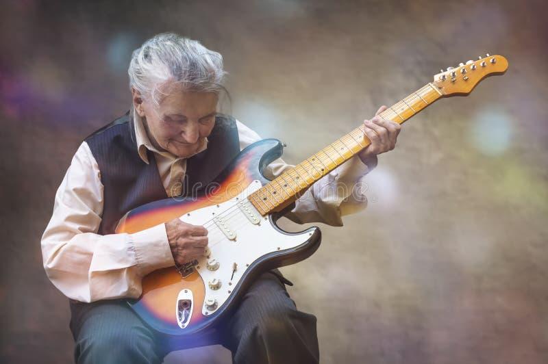 Mulher idosa que joga a guitarra imagens de stock royalty free