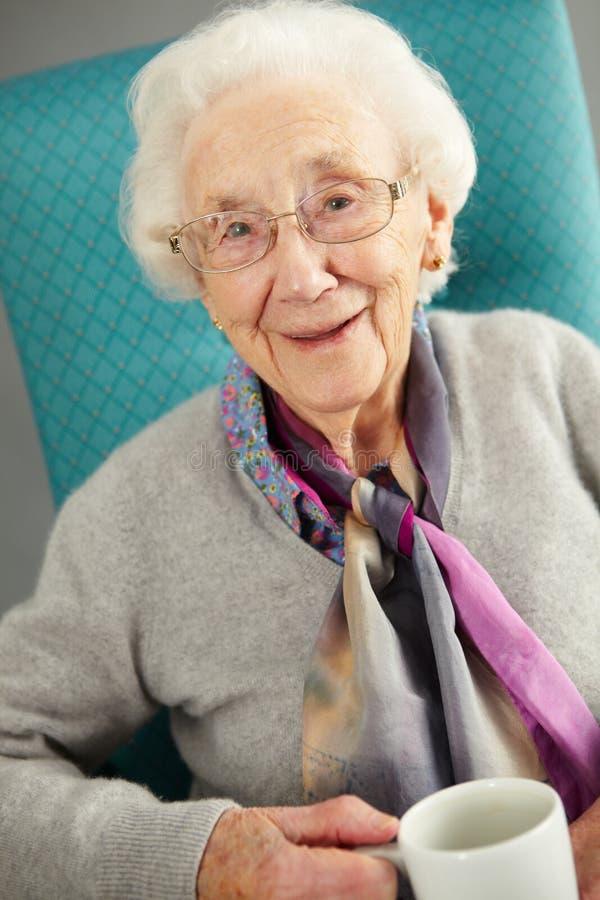 Mulher idosa que olha o chá bebendo confortável foto de stock royalty free