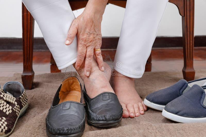 Mulher idosa que põe sobre os pés das sapatas erradamente foto de stock