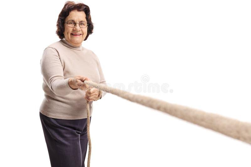 Mulher idosa que puxa uma corda fotos de stock royalty free