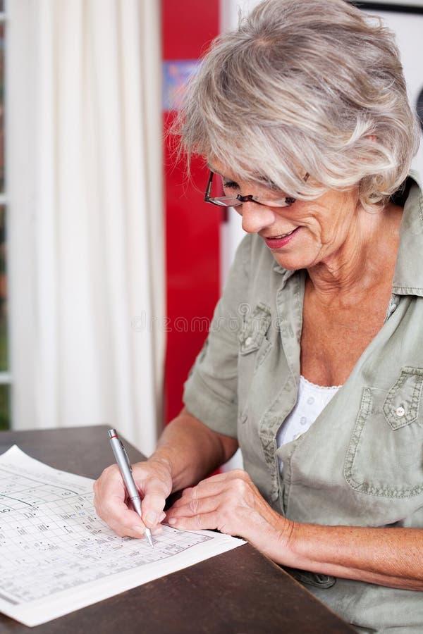 Mulher idosa que resolve umas palavras cruzadas imagens de stock royalty free