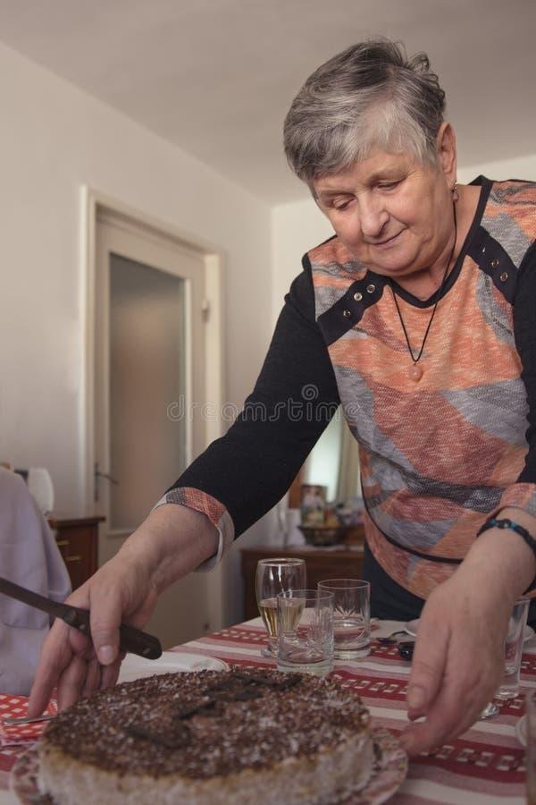 Mulher idosa que serve o bolo no almoço imagem de stock
