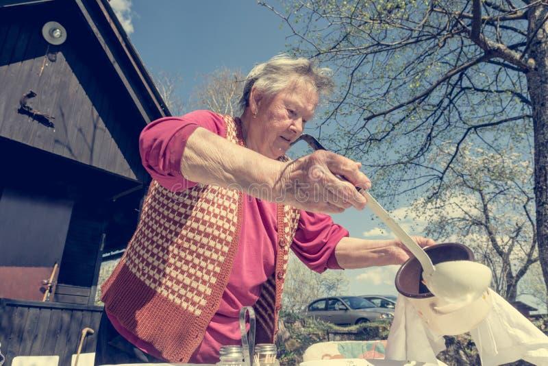 Mulher idosa que serve um almoço exterior fotos de stock royalty free