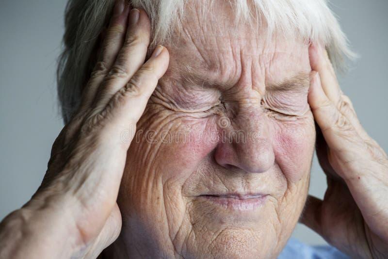 Mulher idosa que sofre da enxaqueca foto de stock royalty free