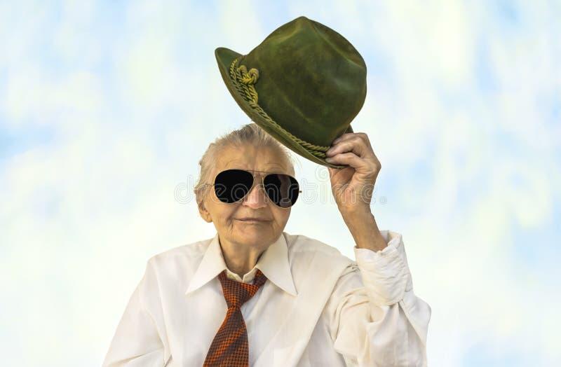 Mulher idosa que sorri com um chapéu em sua mão foto de stock
