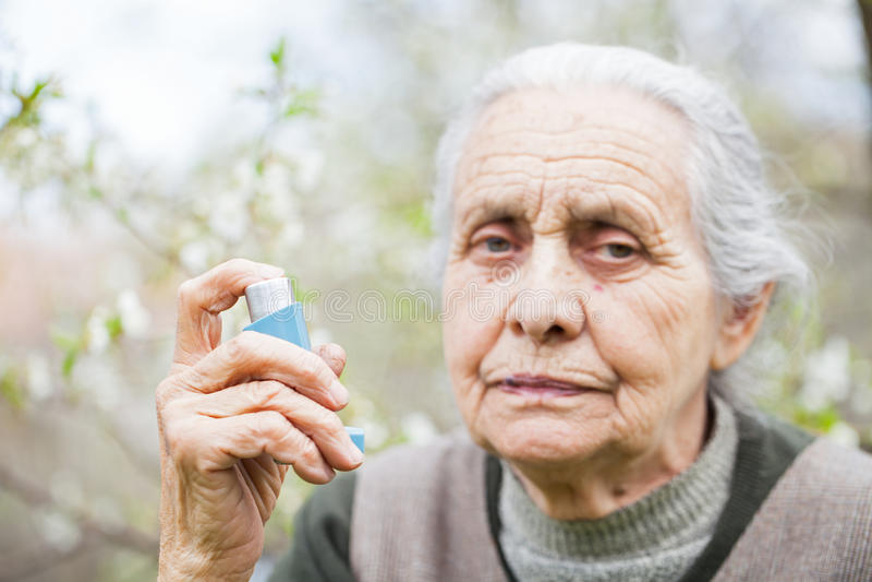 Mulher idosa que tem o ataque de asma, guardando um bronchodilator imagens de stock royalty free