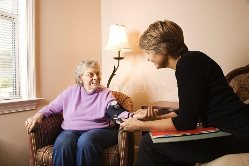 Mulher idosa que tem a pressão sanguínea tomada fotos de stock royalty free