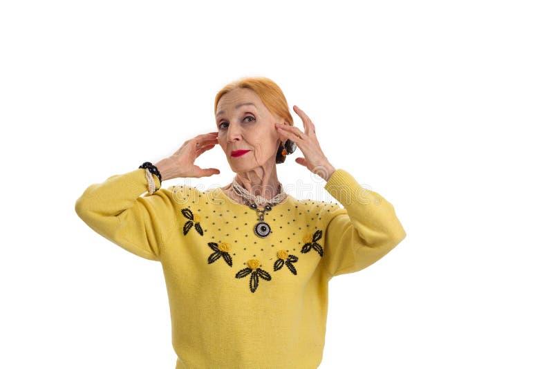 Mulher idosa que toca em sua cara fotos de stock royalty free