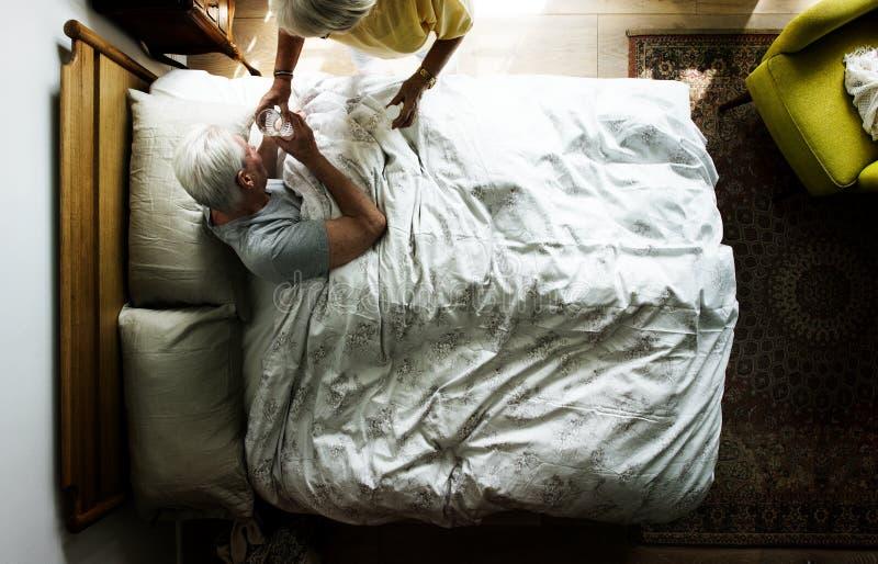 Mulher idosa que toma de um homem idoso fotografia de stock royalty free