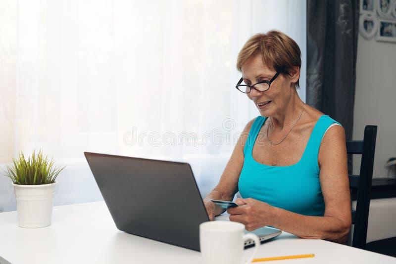 Mulher idosa que usa o laptop e o cartão de crédito fotografia de stock
