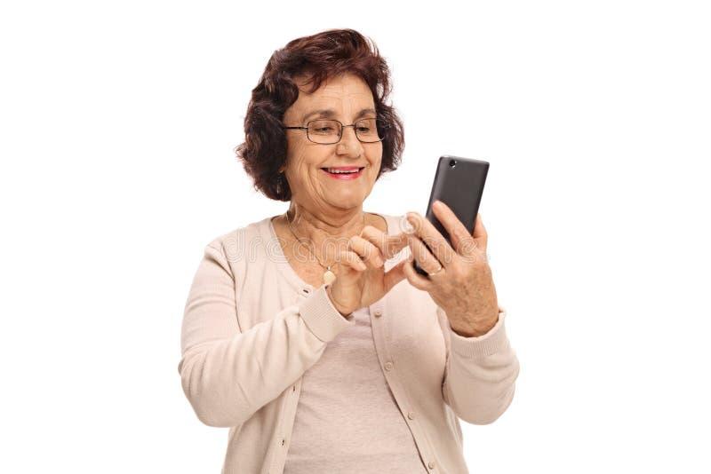 Mulher idosa que usa um telefone e um sorriso foto de stock
