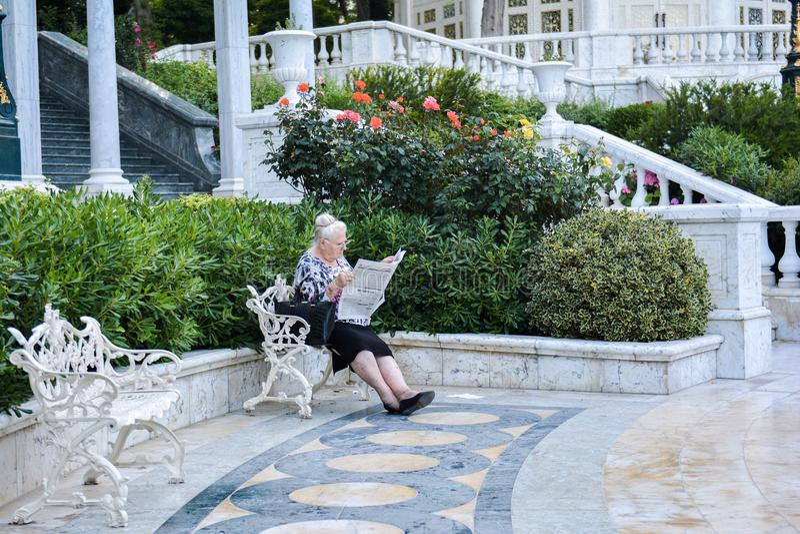 A mulher idosa só lê o jornal imagens de stock royalty free