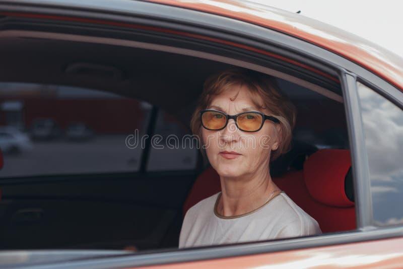 A mulher idosa senta-se no interior do carro fotografia de stock royalty free