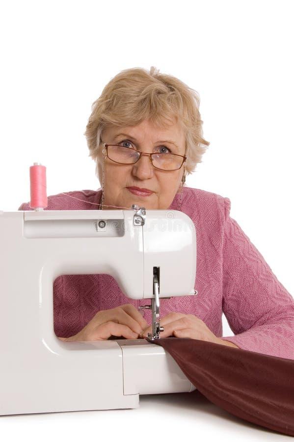 A mulher idosa sews na máquina de costura imagens de stock royalty free