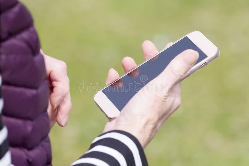 Mulher idosa superior que usa o telefone celular esperto móvel do tela táctil que mostra as mãos velhas imagens de stock royalty free