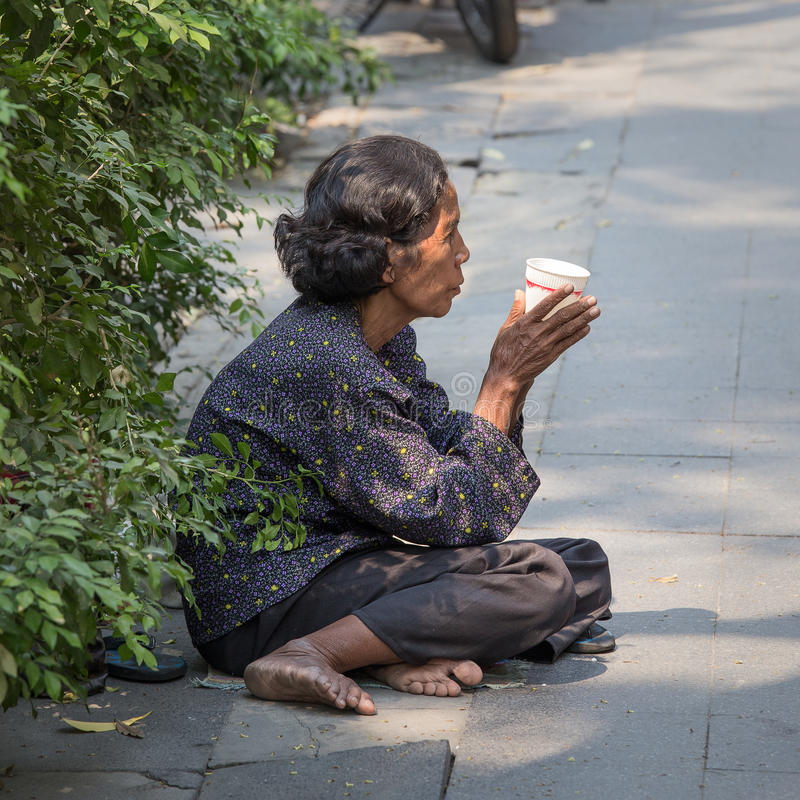 A mulher idosa tailandesa do mendigo espera a esmola em uma rua foto de stock