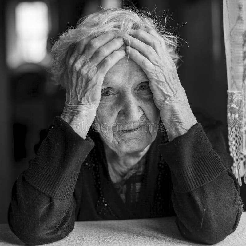 A mulher idosa triste guarda as mãos uma cabeça fotografia de stock royalty free