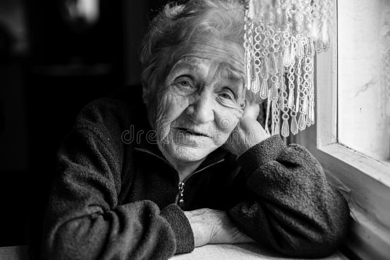 Mulher idosa triste que senta-se perto da janela fotografia de stock royalty free