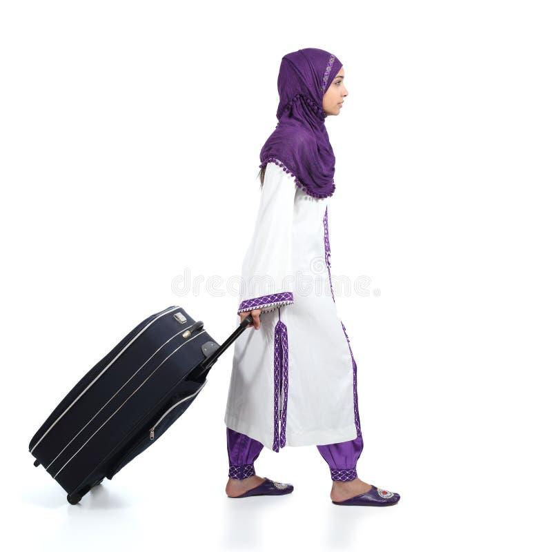 Mulher imigrante muçulmana que veste um hijab que anda levando uma mala de viagem fotos de stock