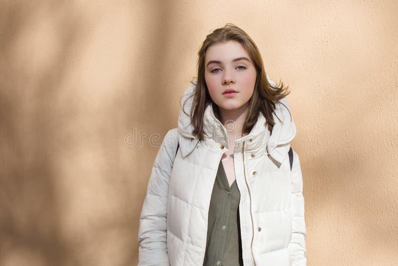 Mulher impertinente bonita nova da estação fria no revestimento branco que levanta contra a parede textured com conceito claro p  foto de stock royalty free