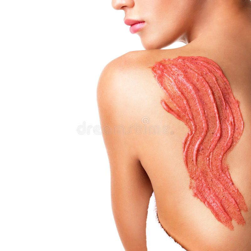 A mulher importa-se com a pele do corpo que usa o cosmético esfrega na parte traseira fotos de stock royalty free