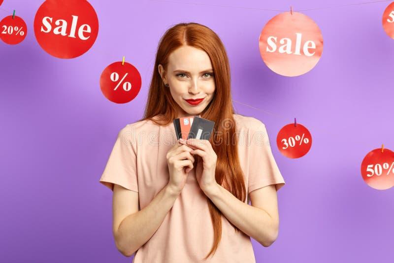 Mulher impressionante bonita feliz que mantém cartões isolados no fundo azul imagens de stock