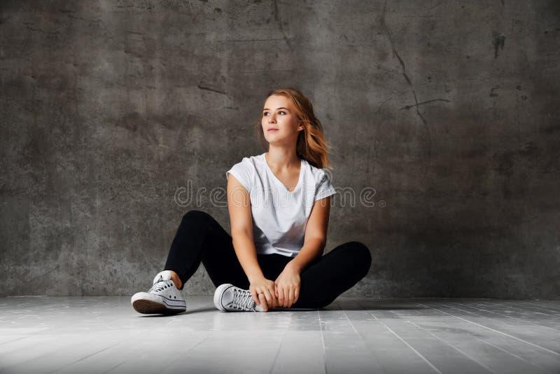 Mulher impressionante com o cabelo louro que levanta na camisa branca vestindo do estúdio e nas calças de brim ásperas pretas, se fotografia de stock