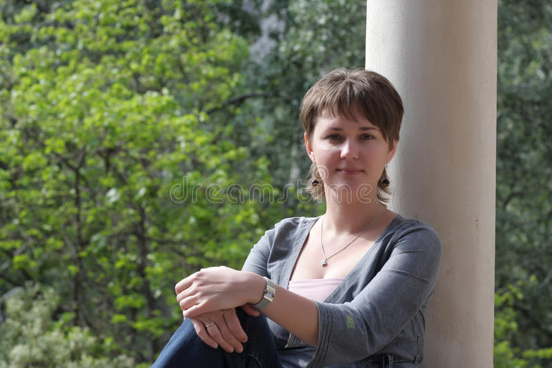 A mulher inclina-se de encontro à coluna foto de stock