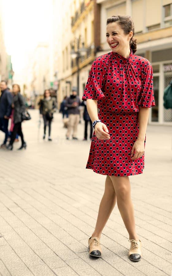 Mulher independente vestida no vermelho que ri muito com emo??es positivas fotografia de stock