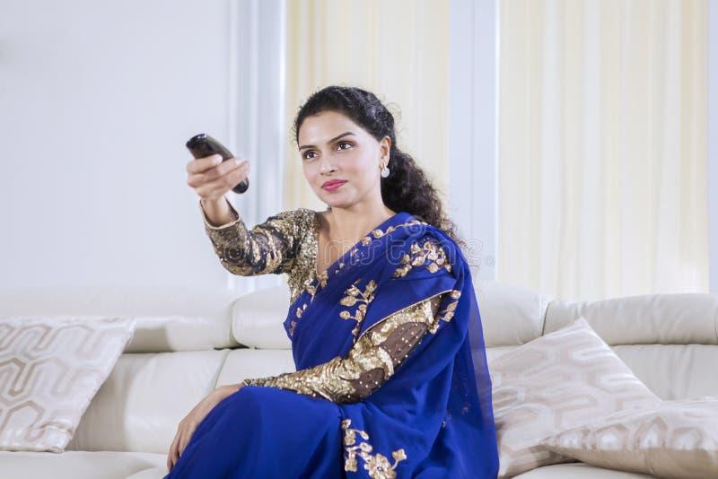 Mulher indiana bonita que olha a tevê em casa foto de stock royalty free