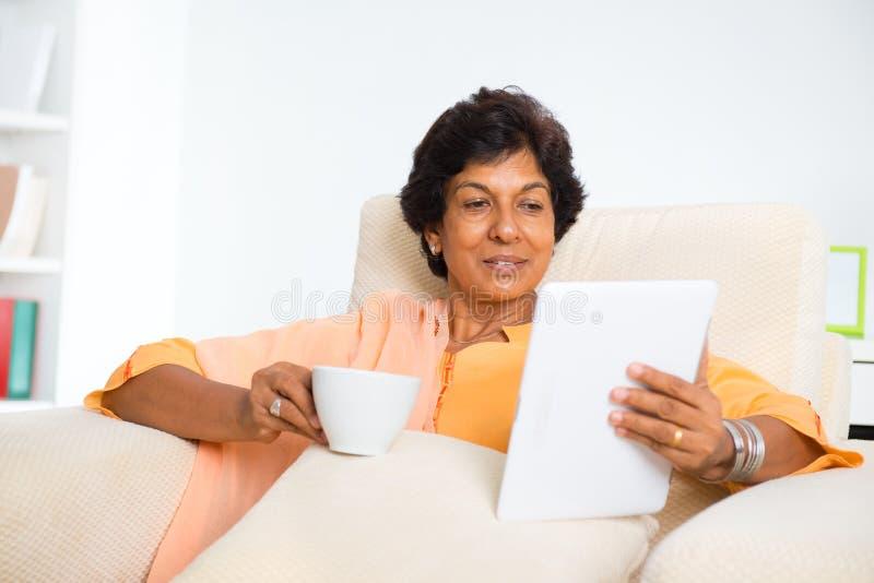 Mulher indiana madura que usa a tabuleta do computador fotografia de stock royalty free