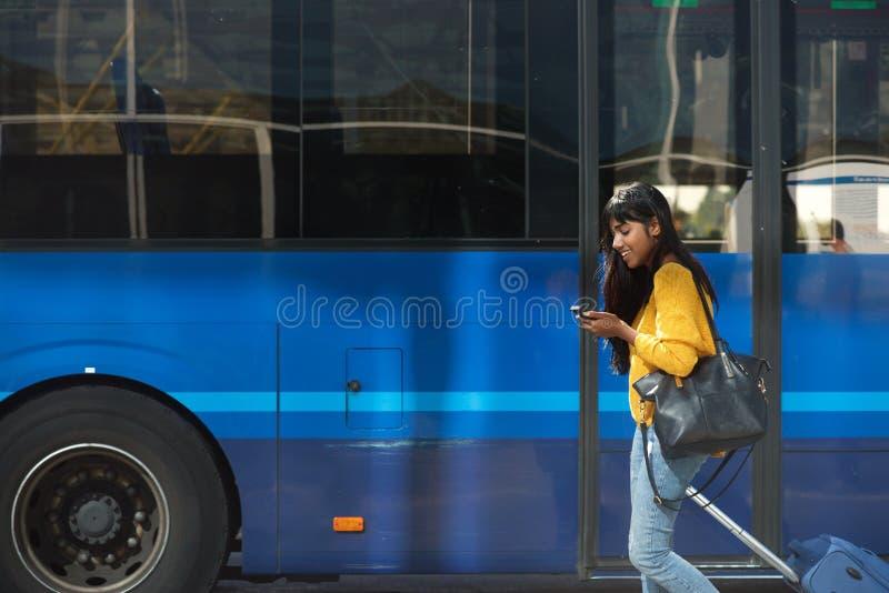 Mulher indiana nova de sorriso que anda com mala de viagem e telefone celular pela estação de ônibus imagens de stock royalty free