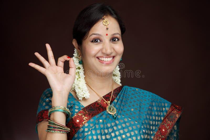 Mulher indiana nova tradicional que faz o sinal APROVADO fotografia de stock royalty free