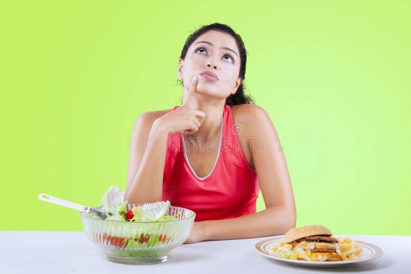 A mulher indiana pensa para escolher o hamburguer ou a salada imagens de stock royalty free