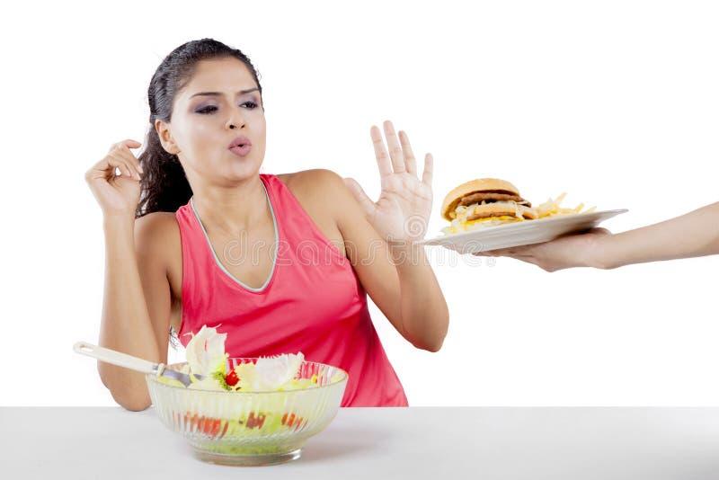 Mulher indiana que rejeita o Hamburger no estúdio imagens de stock