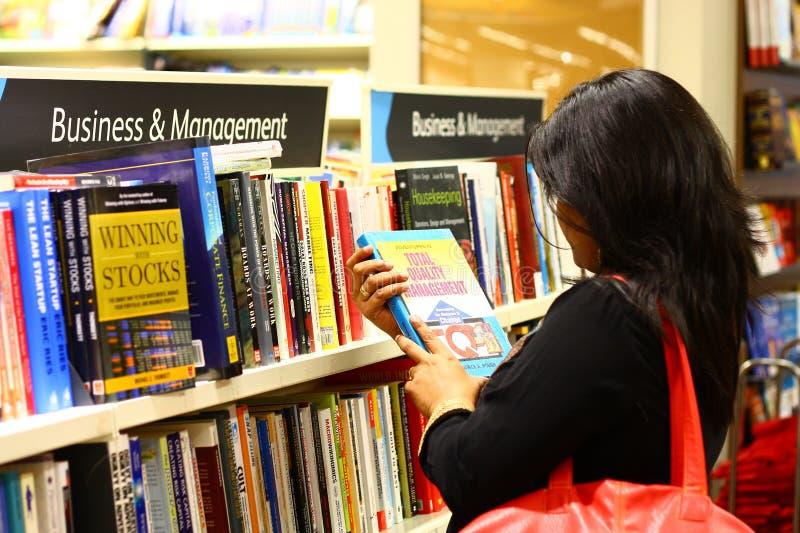 Mulher indiana que seleciona livros da gerência imagem de stock royalty free