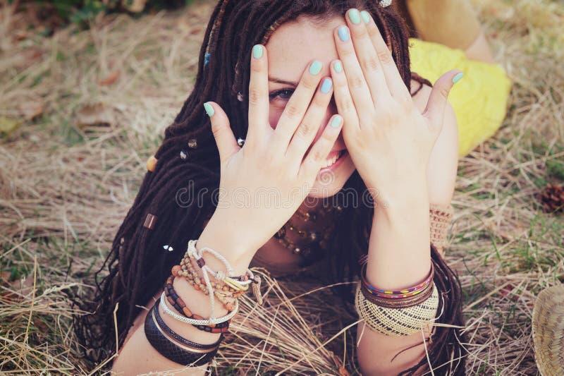 A mulher indie alegre do estilo com penteado dos dreadlocks, tem um divertimento que fecha sua cara com as mãos imagem de stock