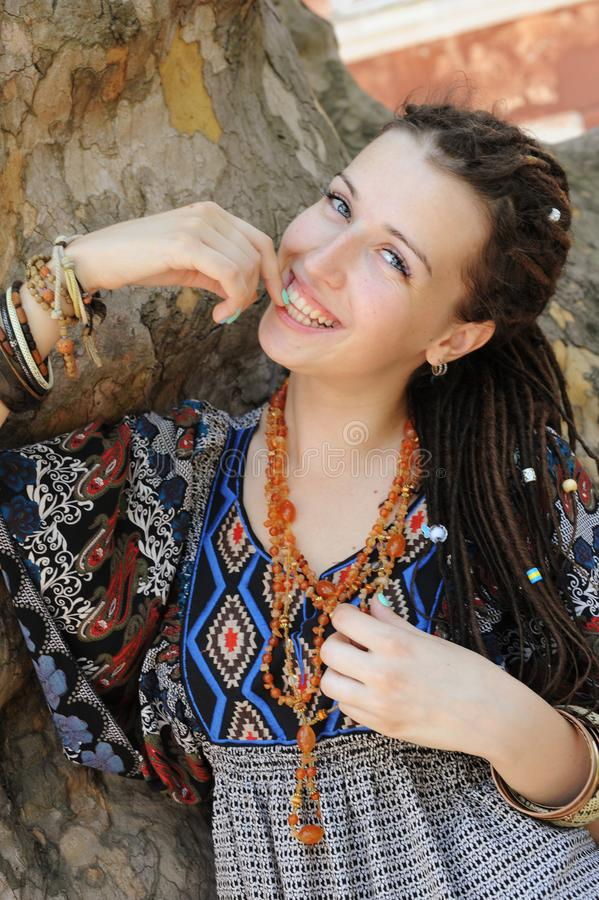 A mulher indie de sorriso feliz do estilo com teme, vestido no vestido decorativo do estilo do boho exterior fotos de stock royalty free