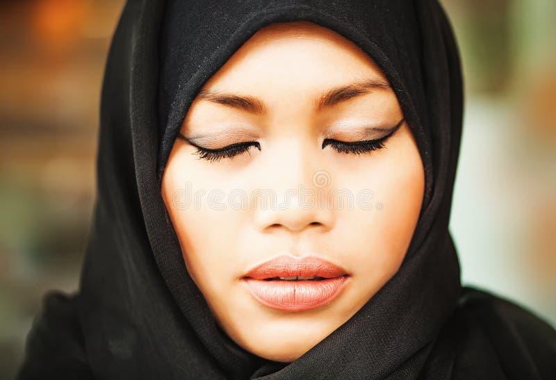 Mulher indonésia muçulmana com olhos fechados fotografia de stock