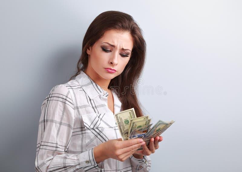 Mulher infeliz nova bonita que olha em dólares e que pensa ho fotos de stock