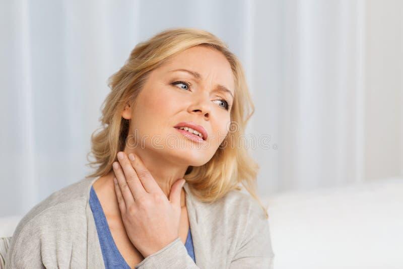 Mulher infeliz que sofre da dor da garganta em casa foto de stock royalty free