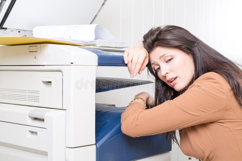 Mulher infeliz triste no escritório com impressora da copiadora foto de stock