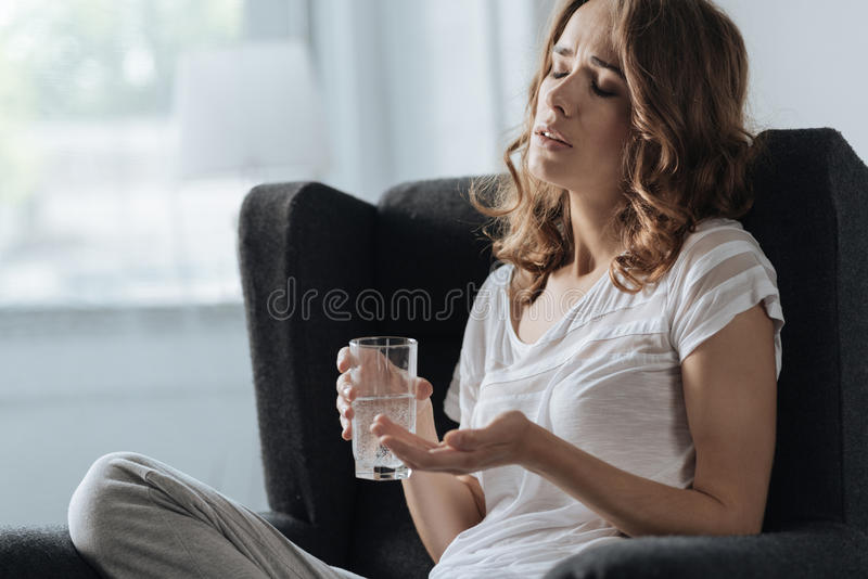 Mulher infeliz triste que guarda um vidro da água foto de stock