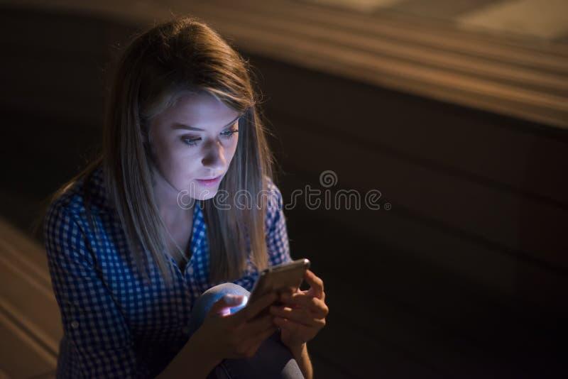 Mulher infeliz virada que guarda o telefone celular no fundo cinzento da parede Menina de vista triste que texting no smartphone fotos de stock royalty free