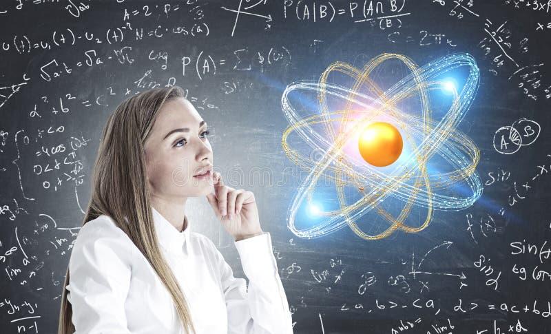 Mulher inspirada que pensa, ciência da física do átomo imagem de stock
