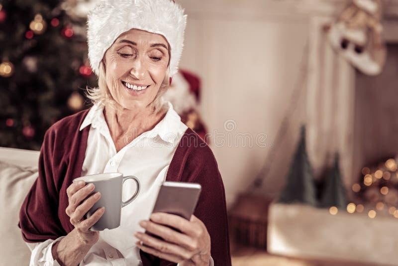 Mulher interessada agradável que sorri e que usa o telefone celular imagem de stock royalty free