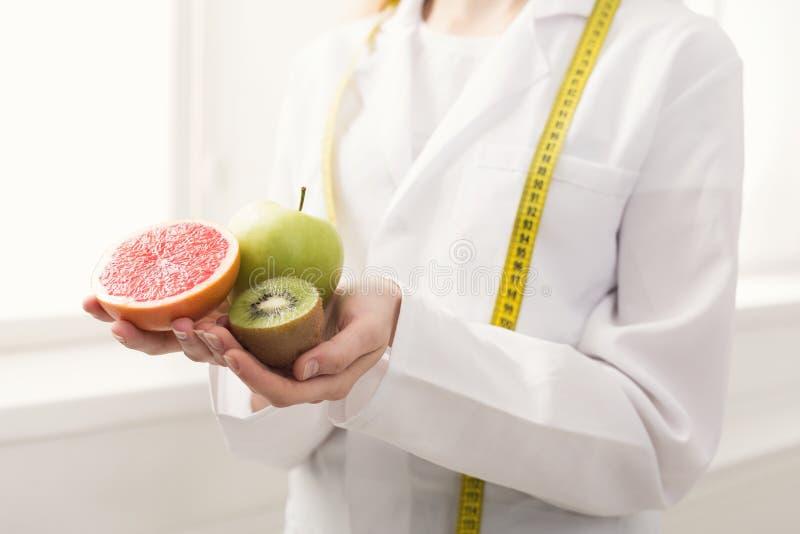 Mulher irreconhecível do nutricionista com frutos no escritório imagens de stock