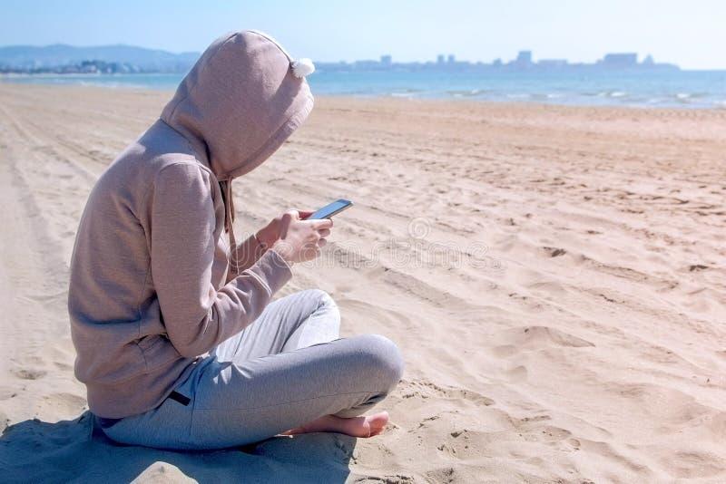 A mulher irreconhecível está datilografando no telefone que senta-se na praia do mar imagem de stock royalty free