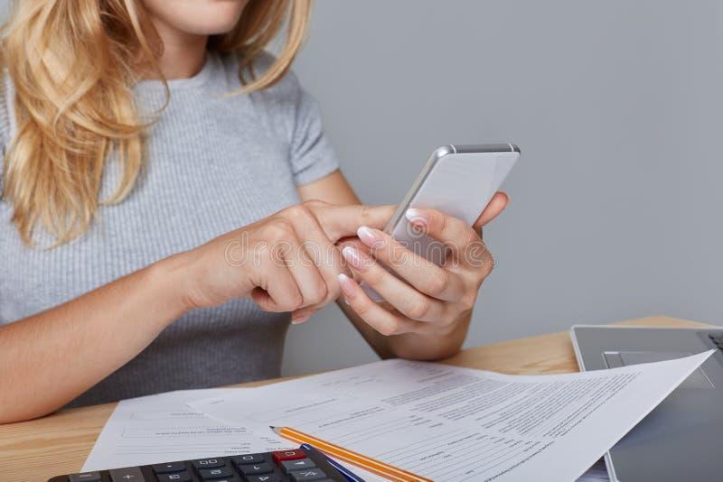 A mulher irreconhecível guarda o telefone celular moderno nas mãos, senta-se na tabela de trabalho, cercada com originais, portát fotografia de stock