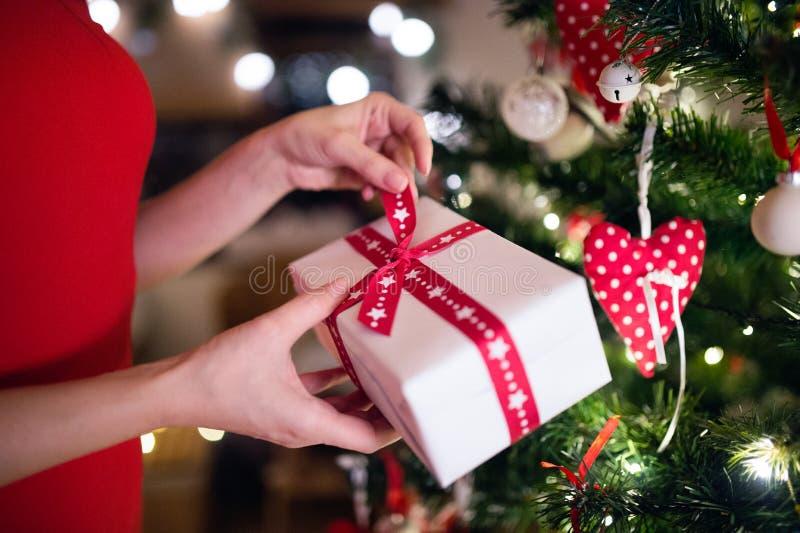 Mulher irreconhecível na frente da árvore de Natal com presente imagens de stock royalty free